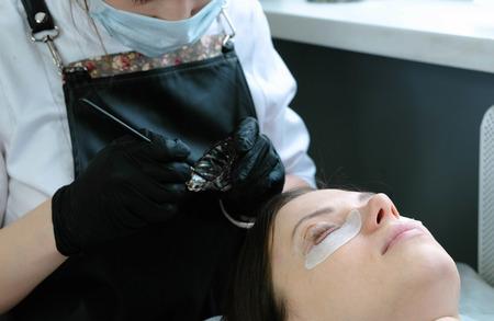 Beauty treatment. Cosmetologist puts black paint on the lashes. Botox and laminating eyelashes.
