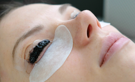 Beauty treatment. Closeup womans face with paint on eyelashes. Botox and laminating eyelashes. Side view.