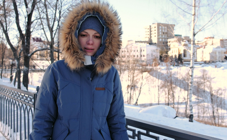 Young woman in blue down jacket with fur hood walking in winter park and freezing on the street. Front view.