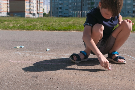 Boy draws with blue chalk on the asphalt. Close-up hands.
