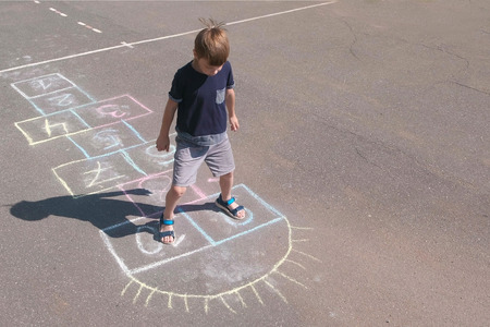 Boy jumps playing hopscotch in the street.
