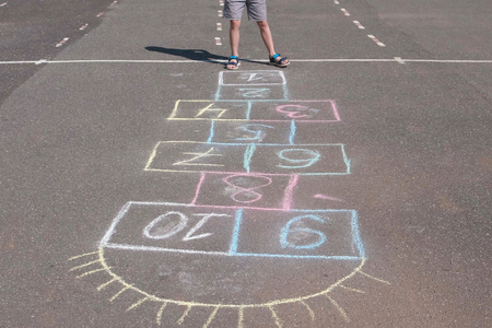Boy jumps playing hopscotch in the street. Close-up legs.
