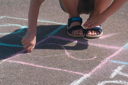 Boy is drawing hopscotch on the asphalt. Close-up hand and legs. Standard-Bild