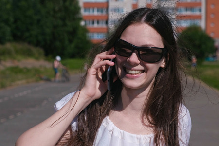 Young brunette girl walking in the stadium in a residential area and talking on a mobile phone.