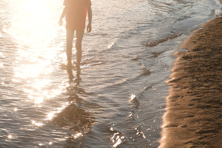 Unrecognizable boy in a red t-shirt walks on the river water. Stock Photo