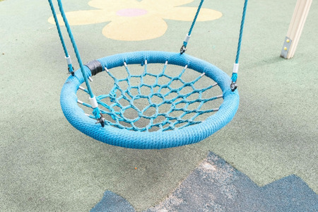 Blue empty webbed swing in playground outdoor.