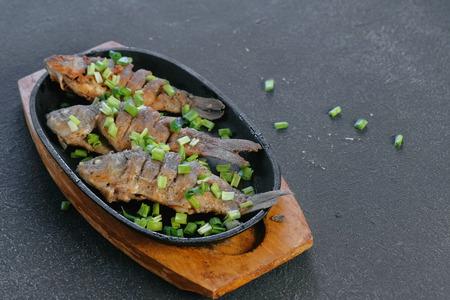 Fried fish carps on a tray sprinkle with green onions. Фото со стока