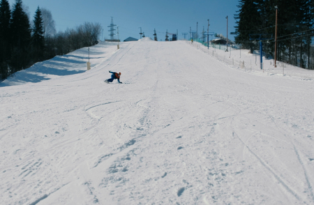 Teenage boy of 12 years sliding on a snowboard from snow descent next sky lift.