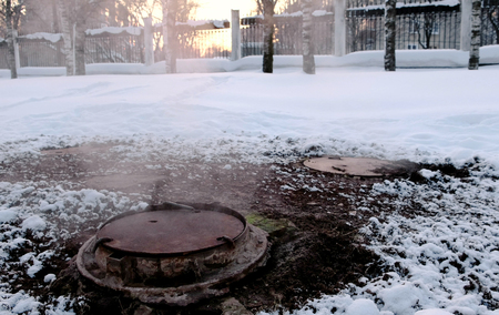 Close-up steam is from sanitary sewer cover in snow in winter park. Melted snow around.