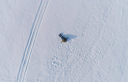 Woman is laying on tubing in the snow. Aerial foto.