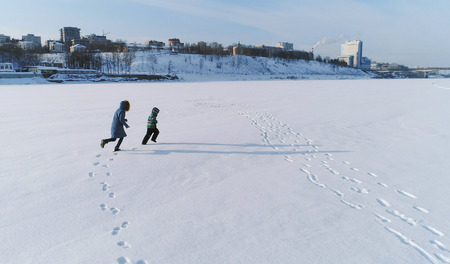 Family time walk and play together. Mother and son running hand in hand through the snow covered area in winter. back view. Aerial foto. Banque d'images - 112550046