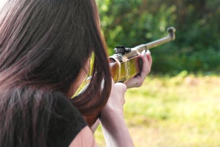 Woman shoots a gun. Back view outdoor. Stock fotó - 112549460