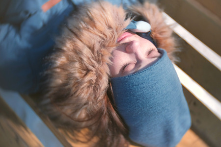 Young woman sleeping in the Park on a bench in the winter. Close-up face.
