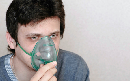 Use nebulizer and inhaler for the treatment. Young man inhaling through inhaler mask. Front view