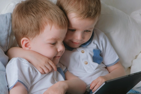 Kids with tablet. Two boys twins toddlers looking cartoon at tablet lying on the bed. Stok Fotoğraf