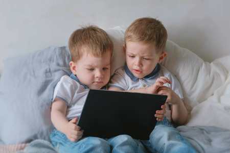 Kids with tablet. Two boys twins toddlers looking cartoon at tablet lying on the bed. Stock Photo