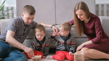 Family mom, dad and two twin brothers play together building out of wooden blocks on the floor.