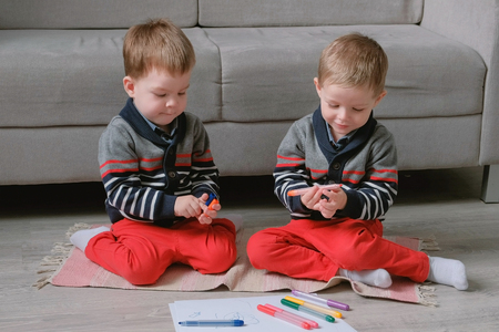Two twin brothers toddlers draw together markers sitting on the floor.