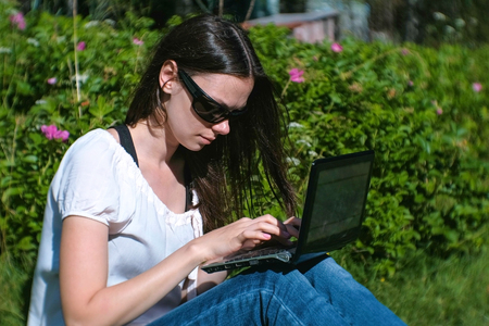 Beautiful brunette girl working typing on laptop sitting in Park in summer.