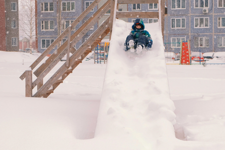 Boy rolls down a snowy wooden slide during a snowfall.