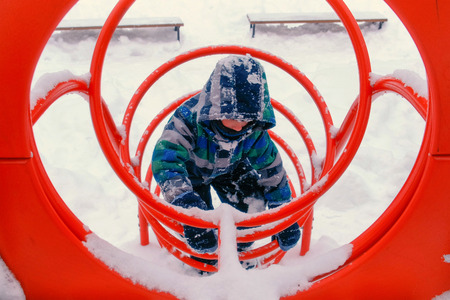 Boy plays on playground in tonnel in winter. 版權商用圖片
