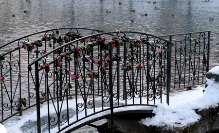 Castles or locks of the newlyweds on the bridge over the pond in the Park. Side view.