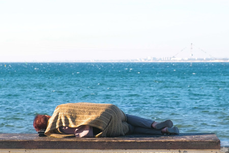 Homeless woman sleeping on a bench on the sea waterfront.