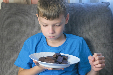 Boy with character. Teen looks at candy and smell them. Concept of unhealthy eating.