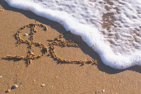 Euro and Dollar signs written in the sea sand. Waves washed away the inscription. Stock fotó