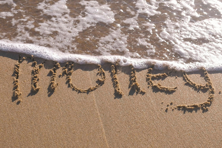 Word Summer written in the sea sand. Waves washed away the inscription. Stock fotó