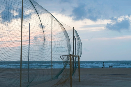 Sports ground with net and gate on the seashore. A man walks with a dog along the coast. 스톡 콘텐츠