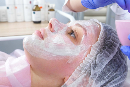 Beautician puts a white mask on the womans face with a brush. Side view. Hands of a cosmetologist in blue rubber gloves. Facial treatments.