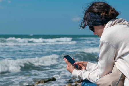 Woman is typing a message on phone sitting on the sea shore in autumn. Stok Fotoğraf