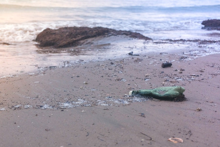 Plastic green bottle and seaweeds on the sand beach at seaside. Stok Fotoğraf