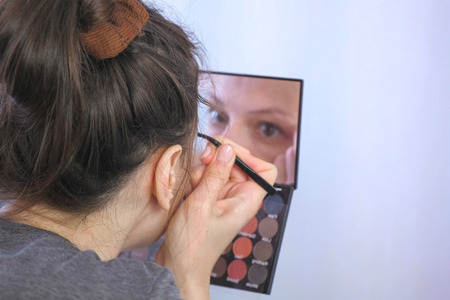 Young brunette woman plucks her eyebrows with tweezers in front of the mirror at home.