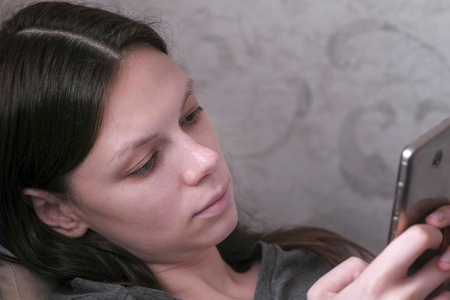 Woman lying on the couch and reading something at the mobile phone. Close-up face. Stock Photo