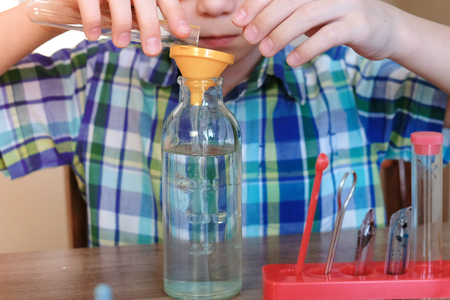Experiments on chemistry at home. Close-up of the boys hands poured water from the tube into the bottle through the funnel.