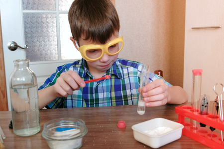 Experiments on chemistry at home. Chemical reaction with the release of gas in a test tube in the hands of a surprised boy.