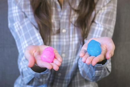 Two slimes pink and blue in womans hands. Playing with slime.