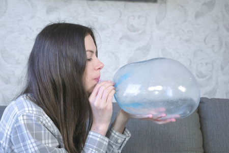 Woman inflates a big bubble from a blue slime. Play with slime.
