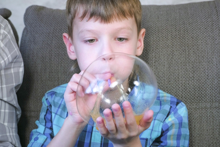Boy inflates a big bubbles from a slimes. Play with slime.
