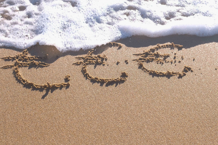 Euro signs written in the sea sand. Waves washed away the inscription.
