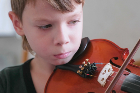 Boy of 8 years is playing violin using notes. Face cloe-up.