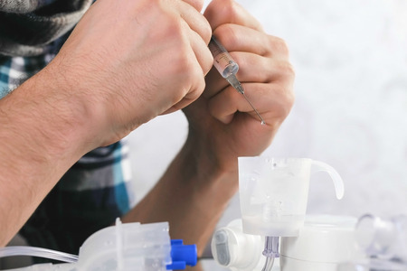 Man pours the saline from the syringe into the container for the inhaler. Hands close-up.