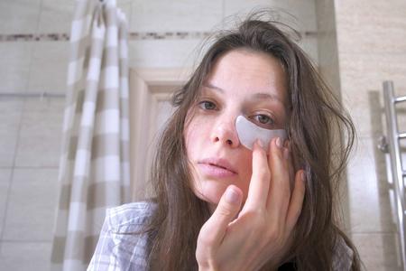 Una donna stanca e svegliata con i postumi di una sbornia mette delle bende sugli occhi in bagno. Archivio Fotografico