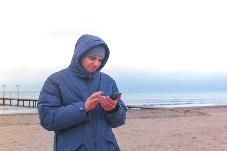 Man in a blue down jacket on the sand beach by the sea typing a message on mobile phone. 写真素材