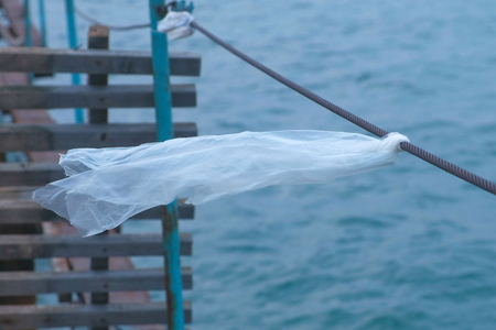 Plastic bag is tied to the cable of the sea pier.