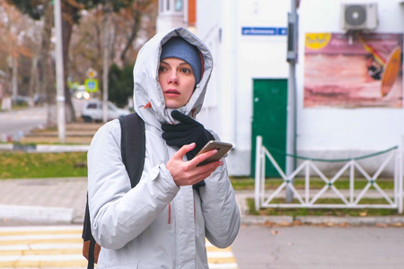 Woman got lost in the city and looking for a route using the Navigator in the mobile phone.