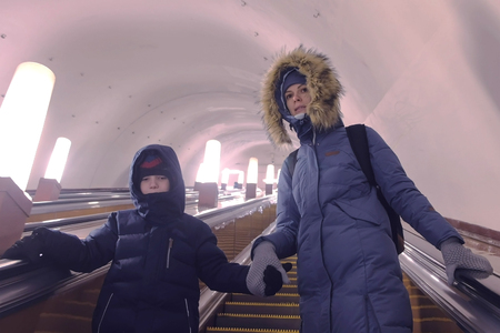Mom and son in winter clothes are moving up the escalator in the subway tunnel.
