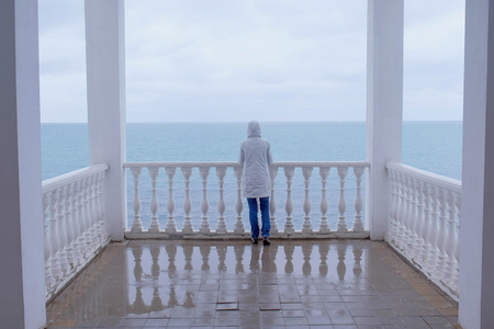 Woman in the white jacket admires at sea on beautiful terrace with sea view. Back view.